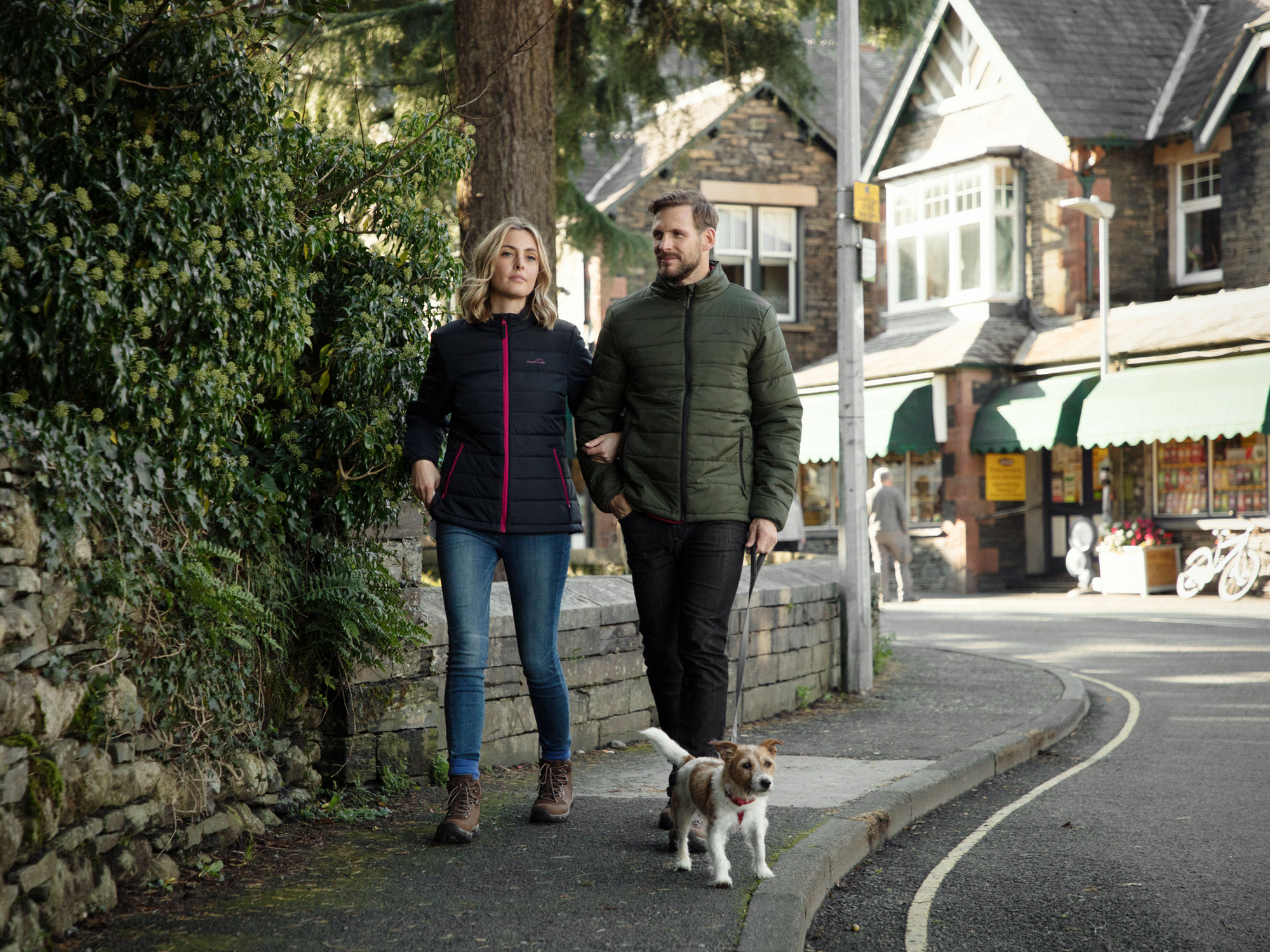 male and female couple walking dog along high street